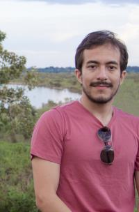 Alonso is standing with a green landscape behind him, in a red shirt and sunglasses hanging on his collar.