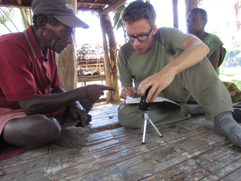 Graduate student Joseph Brooks working with a consultant in Papua New Guinea