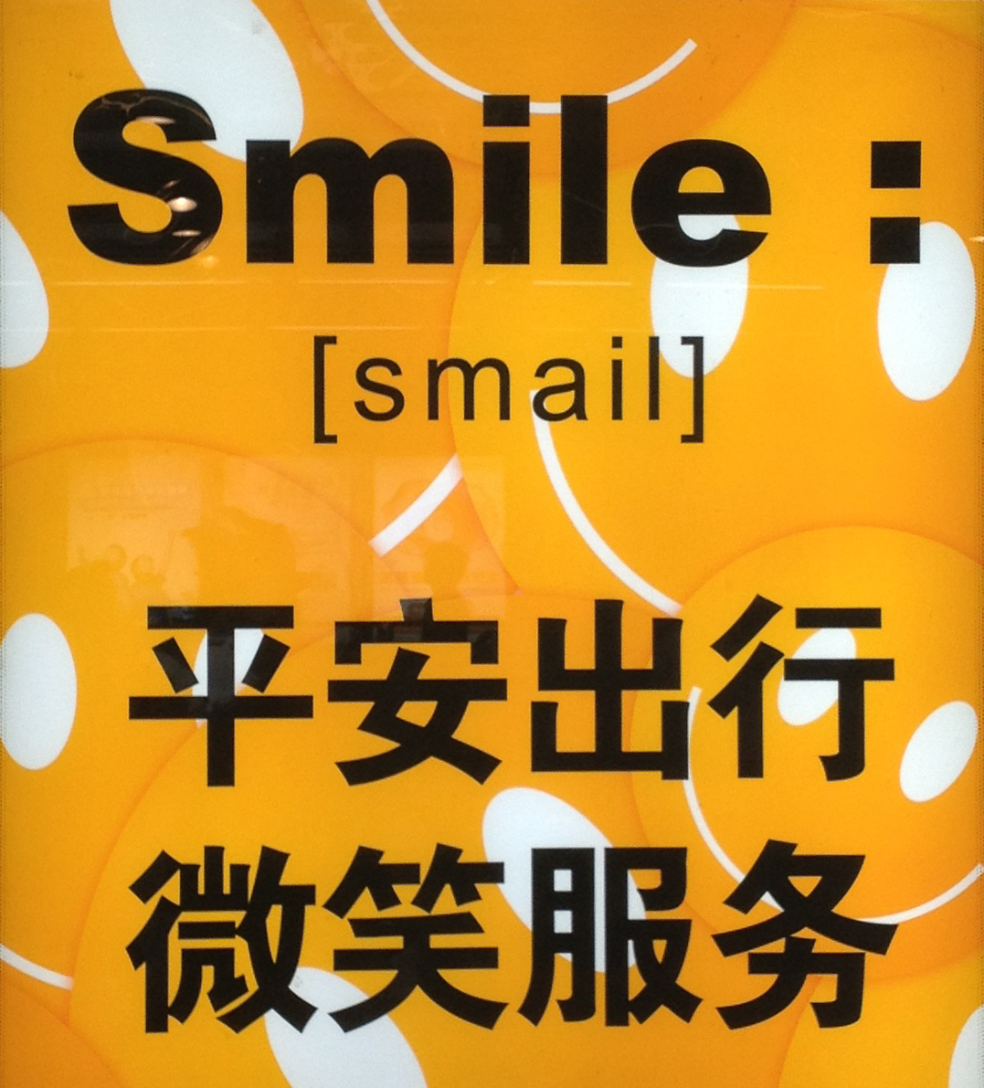 "A sign with the word ""Smile"" written in a variety of ways"